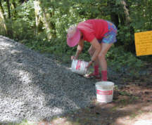 Fill a bucket from the gravel pile.